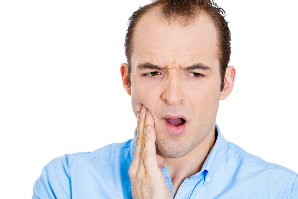 man with hand on face - has a toothache