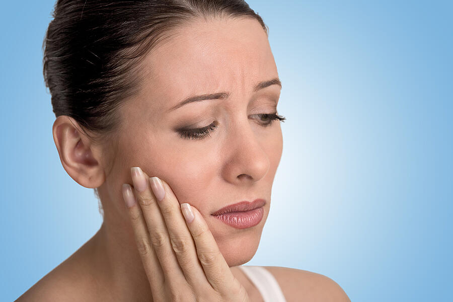 Closeup portrait young woman with sensitive tooth ache crown problem about to cry from pain touching outside mouth with hand isolated blue background. Negative emotion facial expression feeling