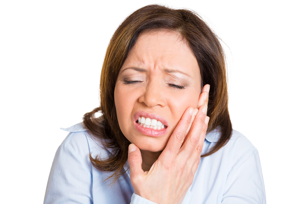 Closeup portrait, mature woman with sensitive tooth ache crown problem about to cry from pain touching outside mouth with hand, isolated white background. Negative emotion facial expression feeling