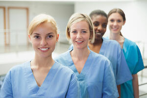 Female nurse looking at camera in hospital hallway