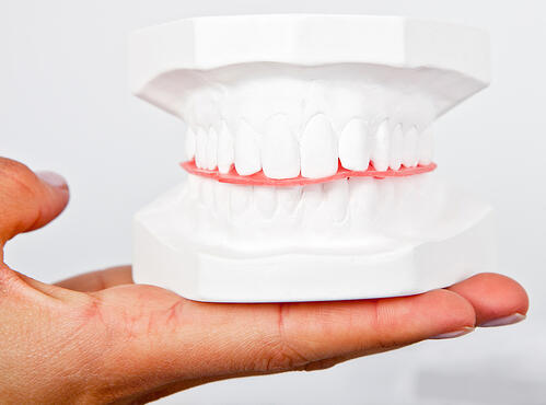 Man holding a teeth sample made out of plaster cast-1