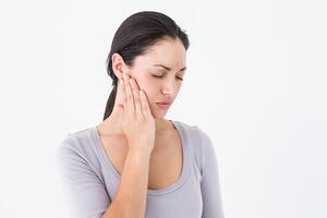 Woman suffering from teeth pain on white background