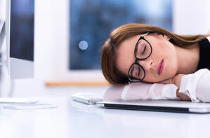 Young businesswoman in glasses sleeping at her workplace
