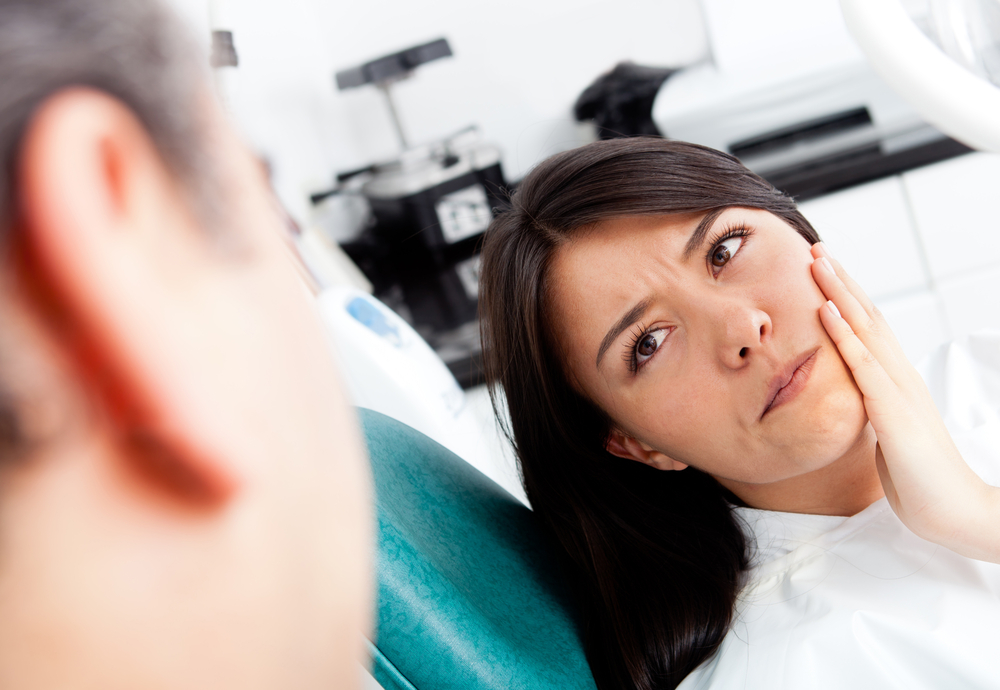 Woman at the dentist complaining about a tooth pain