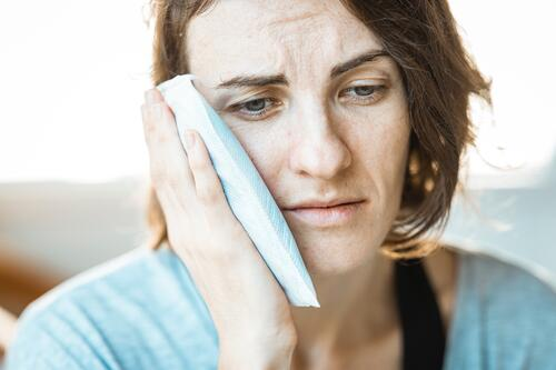 Northwest Oral Surgery Soft Tissue Facial Injuries Woman Holding Cold Pack on Aching Jaw