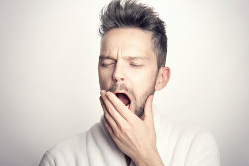 NW Oral Surgery Is It Time to Consider Surgery for TMJ Issues Man in White Shirt Holding Jaw in Pain